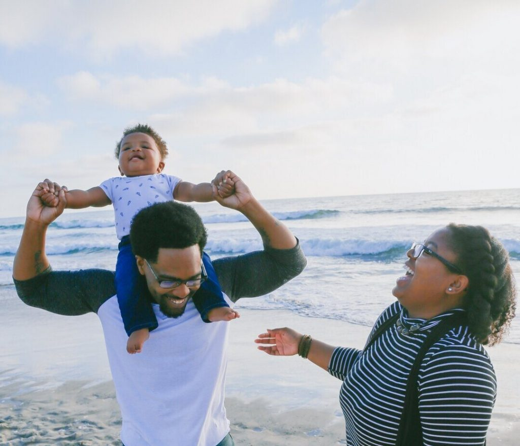 With the child sitting on his father's shoulders, the family of three stands happily on the beach and enjoys their private adventure