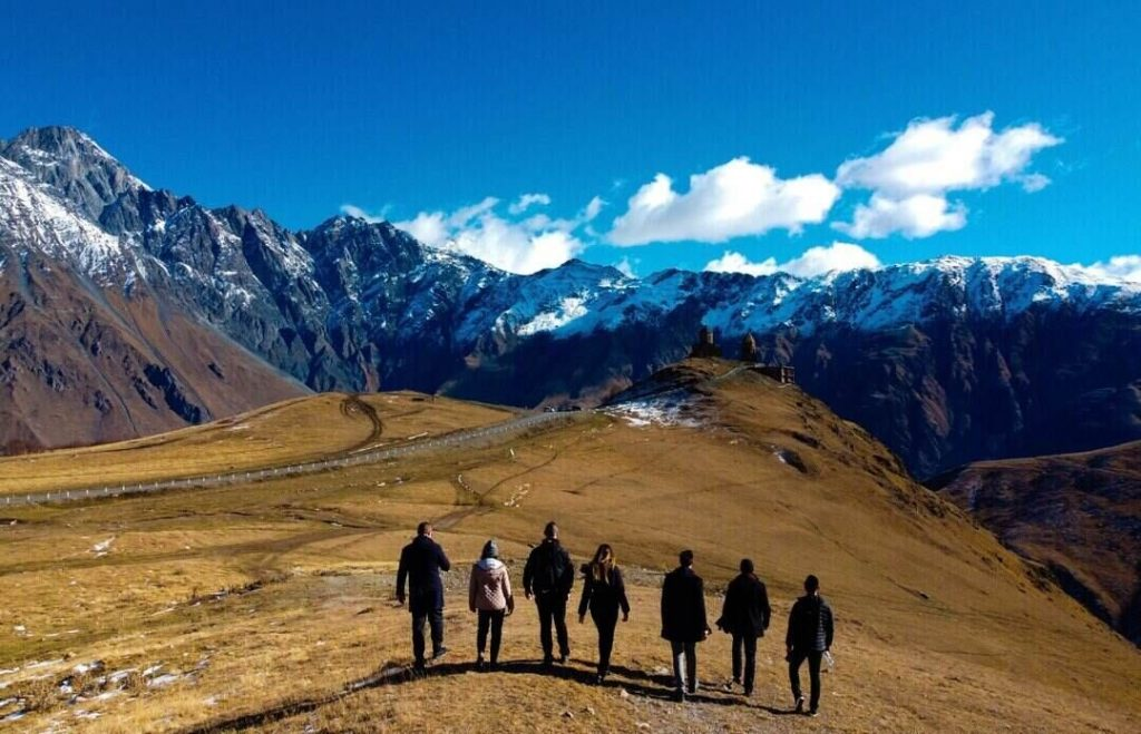 A group of people are walking through gorgeous mountain landscape