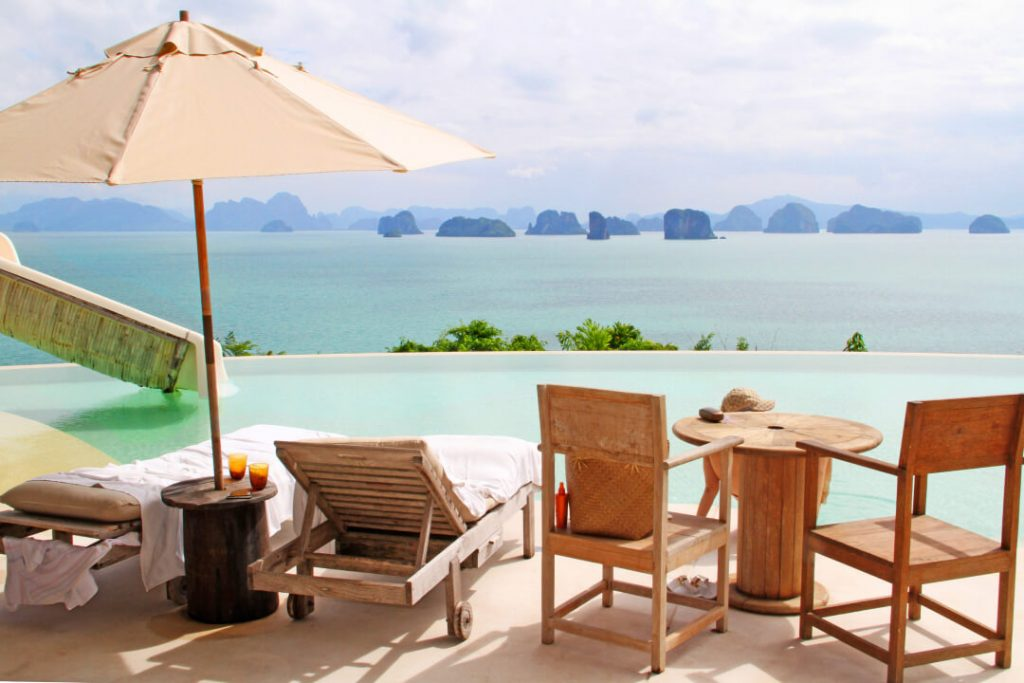 Poolside chairs and an umbrella from a resort in Koh Yao Noi, Thailand, overlook the beautiful Phang Nga Bay.