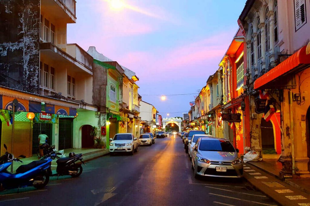 A night time view of the Old Town Phuket, Thailand street with cars parked on either side and lights casting a nice yellow glow.