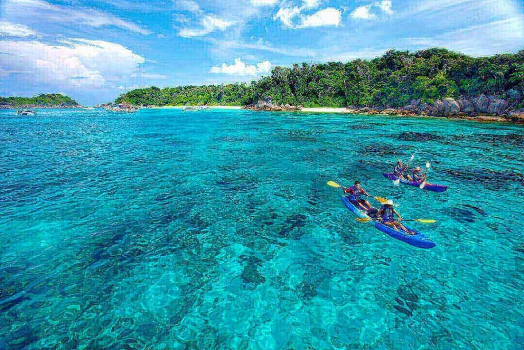 Two kayaks, each with two people in them, explore the beautiful blue waters of the Similan Islands, Thailand.