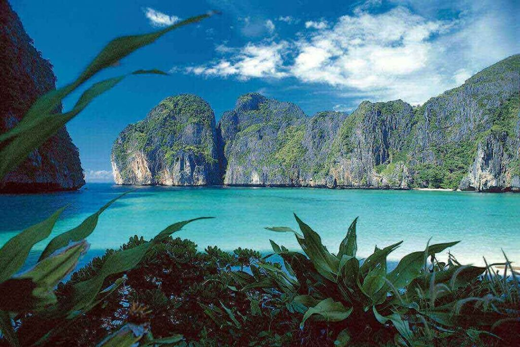 A stunning view of Phi Phi Island, Thailand, with its limestone rocks, emerald water, and surrounding jungle.