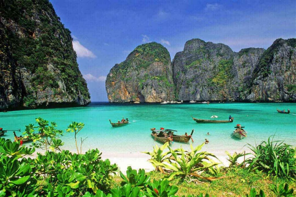 Thai long-tail boats float in the famous Maya Bay, which served as the filming location for the movie The Beach.