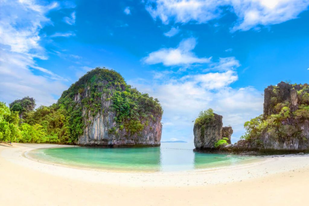A beautiful image of a Phuket, Thailand beach with no one around but the limestone rocks, emerald water, and golden sandy beach.