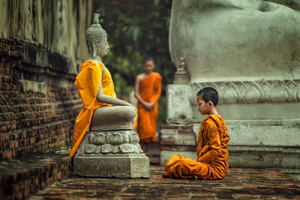 A young monk can be seen meditating in front of a Buddha statue  in a temple in Thailand.
