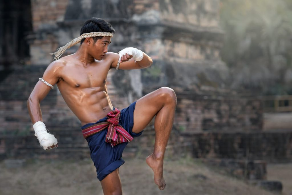 A young man stands with his left leg bent in a martial arts stance as he practices Muay Thai outside a temple in Thailand.