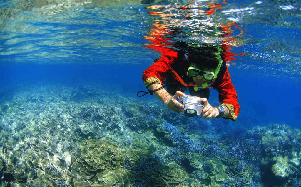 A person snorkels with a camera in the crystal clear water of the Mu Koh Surin National Park, Thailand.